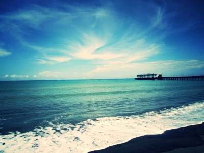 View of ocean, blue sky, swirl of white clouds, pier