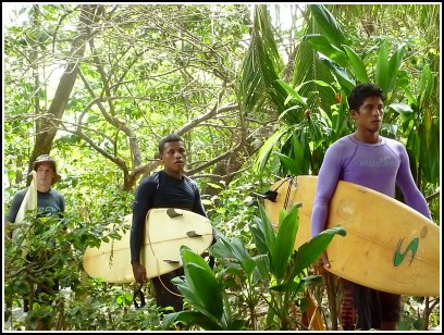 3 guys walking with surfboards through the jungle