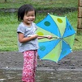 Little girl in rain with umbrella to the side