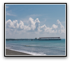 VIew of blue sky, white clouds, blue ocean with a pier