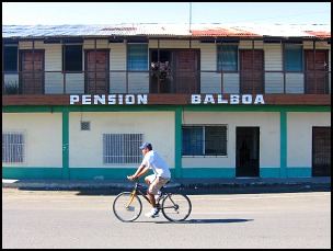 Bicyclist riding down street in front of Pension Balboa