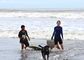 Girl, boy, and dog playing at the beach