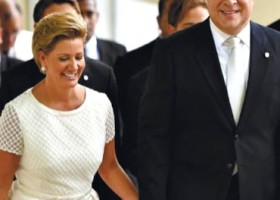 First lady, in white dress, and President Varela in suit holding hands