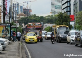 Street in Panama City with buses, cars, motorcycle, and pedestrians