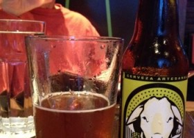 Glass of beer with bottle of Chivopero IPA next to it and man behind drinking a glass of beer